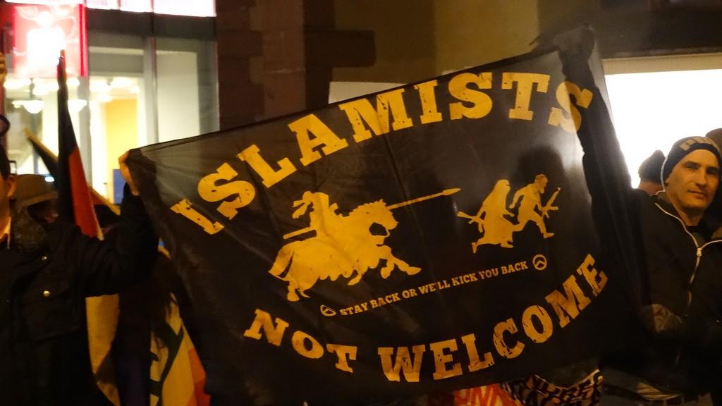 Des membres de Pegida brandissent un drapeau islamophobe.